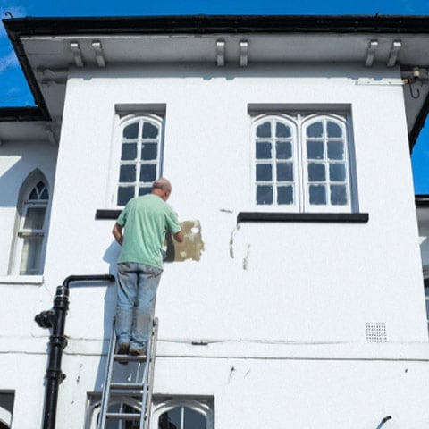 homeowner painting outside of his home
