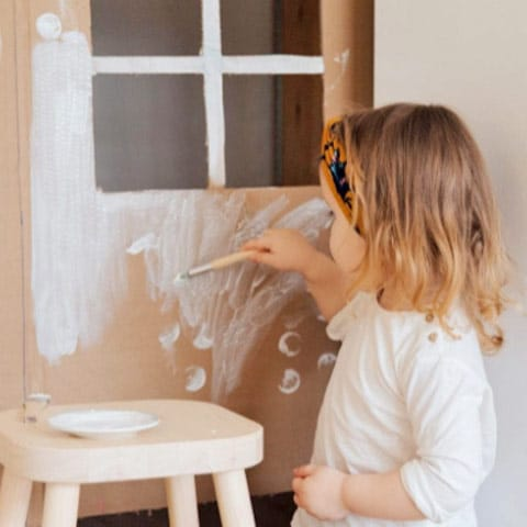 young girl painting wall