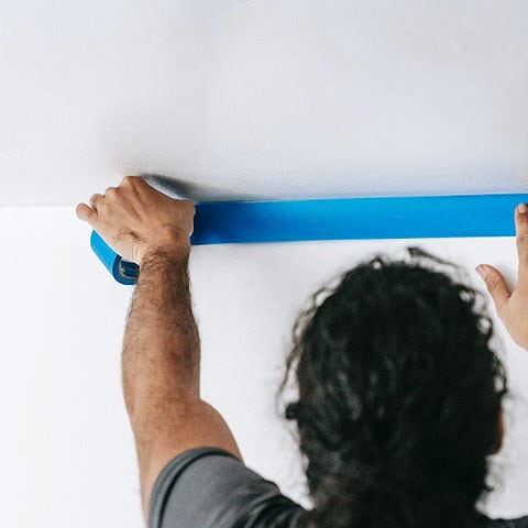 Painter using blue tape on walls